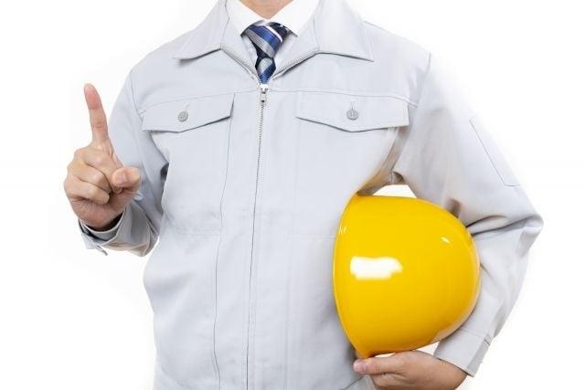 ヘルメットを持って指を立てる作業服の男性